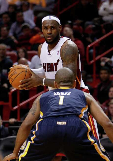 Miami Heat forward LeBron James, rear, looks for an open teammate past Indiana Pacers guard Dahntay Jones during the second half of an NBA basketball game, Wednesday, Jan. 4, 2012, in Miami. The Heat defeated the Pacers 118-83. (AP Photo/Wilfredo Lee) Photo: Wilfredo Lee / AP