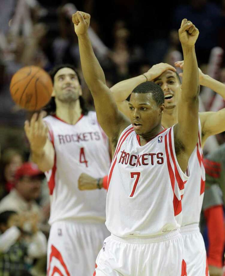 Rockets players such as Kyle Lowry (7), Luis Scola (4) and Kevin Martin were more relieved than excited to have escaped with an overtime victory when the Hornets' Marco Belinelli missed a shot at the buzzer. Photo: Melissa Phillip / © 2011 Houston Chronicle