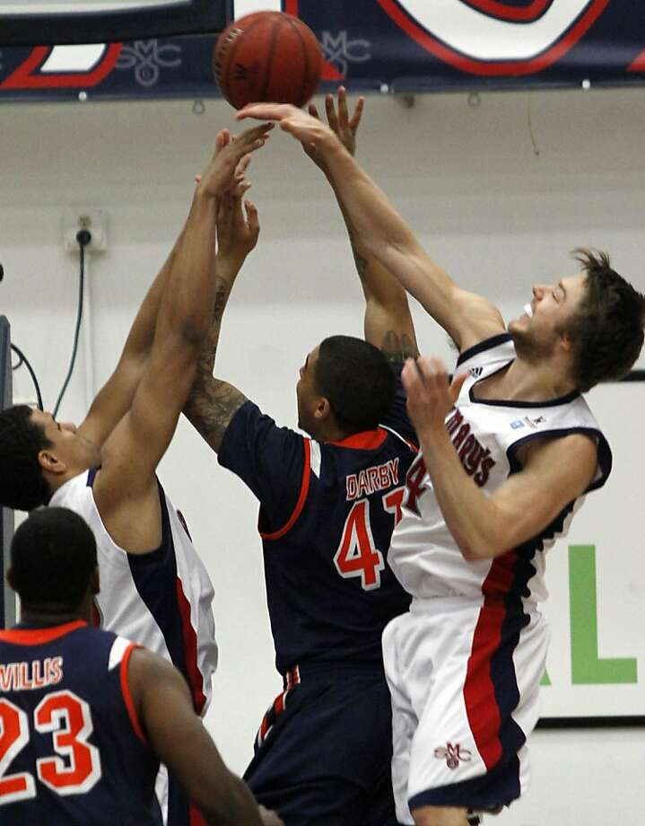 Pepperdine's Taylor Darby, center, shoots as St. Mary's Brad Waldow, left, and Matthew Dellavedova defend during the first half of an NCAA college basketball game, Thursday, Jan. 19, 2012, in Moraga, Calif. (AP Photo/George Nikitin) Photo: George Nikitin, Associated Press