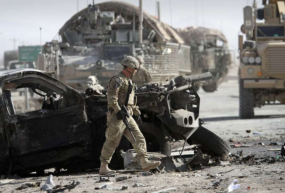 A U.S. soldier with the NATO led International Security Assistance Force (ISAF) walks past by a damaged vehicle at the scene of a suicide attack in Kandahar south of Kabul, Afghanistan, Thursday, Jan. 19, 2012. A suicide attacker blew himself up Thursday at an entrance to a sprawling base for U.S. and NATO operations in southern Afghanistan, killing at least six civilians, police said. (AP Photo/Allauddin Khan) Photo: Allauddin Khan, Associated Press