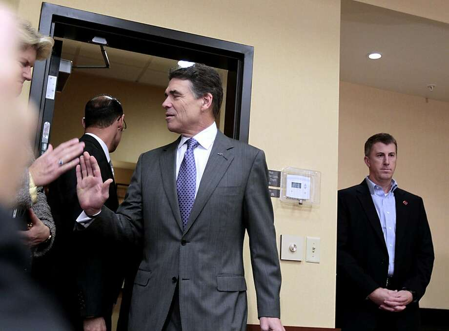 Republican presidential candidate Texas Gov. Rick Perry gets a high-five as he enters a press conference to announce he is suspending his campaign and endorsing Newt Gingrich Thursday, Jan. 19, 2012, in North Charleston, S.C. (AP Photo/David Goldman) Photo: David Goldman, Associated Press