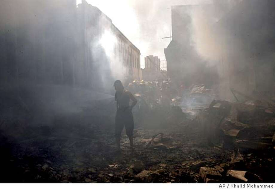 A man walks through the rubble just after a suicide car bomb exploded in Baghdad, Iraq, Monday, March 5, 2007. A suicide car bomber struck near the well-known Mutanabi book market in central Baghdad Monday, killing at least 26 people and injuring more than 50, in a first major blast in the city in several days, police said. (AP Photo/Khalid Mohammed) Photo: KHALID MOHAMMED