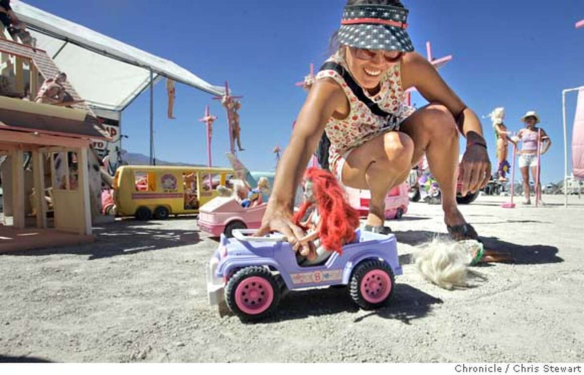 Yasmin Ward, 30, of Kauai drags a Barbie doll at the Barbie Death Camp and Wine Bistro on the playa at Burning Man 2005, Tuesday, August 30, 2005 in the Black Rock desert. burnman2005 Chris Stewart / The Chronicle