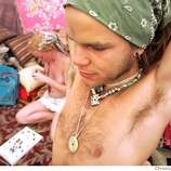"Brian Decosse, 21, from ""here and there,"" tries on his completed necklace while Heather Flikkema (cq), 26, of Seattle works on her own as Burners crowd the Necklace Factory at Burning Man 2005, Tuesday, August 30, 2005 on the playa at Black Rock desert. burnman2005  Chris Stewart / The Chronicle"