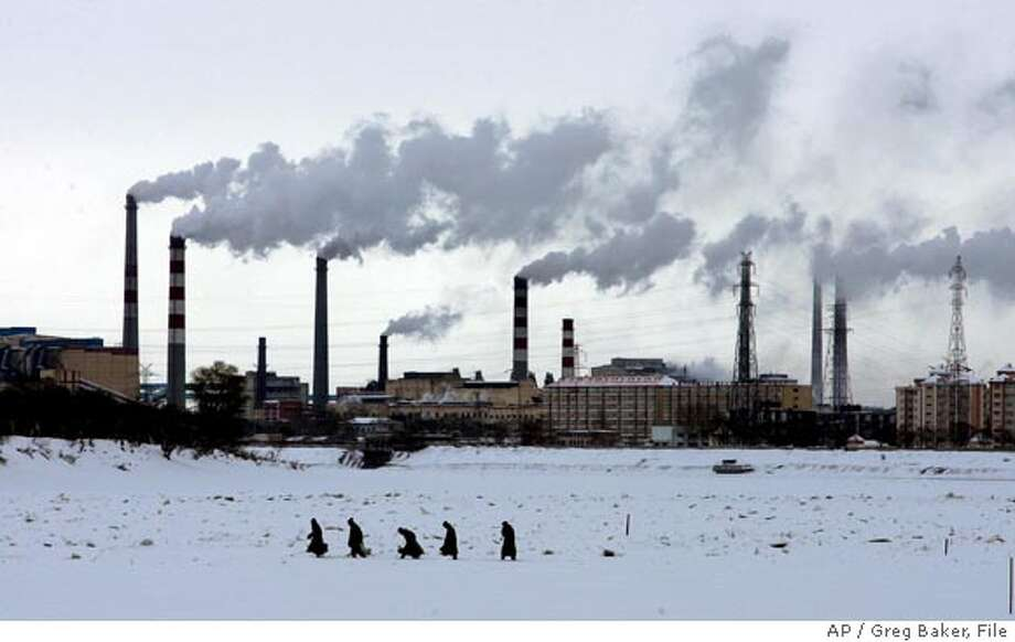 ** FILE ** Residents walk across the frozen Songhua River in front of smoke stacks at Jiamusi, in China's northeast Heilongjiang province in this Dec. 4, 2005 file photo. China is concerned about global warming but lacks the money and technology to significantly reduce its own greenhouse gas emissions that are worsening the problem, a top government scientist said Tuesday, Feb. 6, 2007. (AP Photo/Greg Baker, File)  Ran on: 03-05-2007  Residents walk across the ice-covered Songhua River in front of smoke stacks at Jiamusi, in Heilongjiang province. China lacks the technology to reduce its emissions.  Ran on: 03-05-2007  Residents walk across the ice-covered Songhua River in front of smokestacks at Jiamusi, in Heilongjiang province. China lacks the technology to reduce its emissions. Photo: Greg Baker