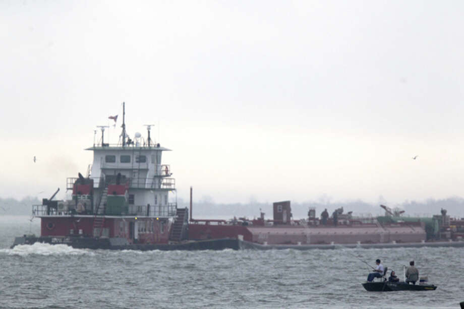 A barge leaves the Port of Houston at Barbours Cut Terminal next to a fishing boat after entry into and out of the port was suspended due to fog early Friday, Jan. 20., 2012. Photo: Johnny Hanson, (Johnny Hanson / Chronicle)