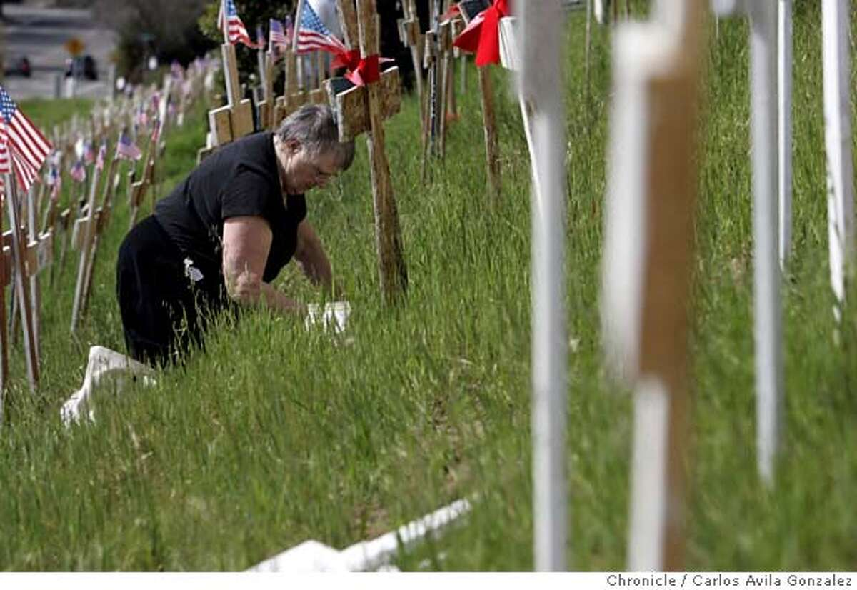 CROSSES05_009_CAG.JPG Audrey Pratt of Martinez plants flowers at the base of a cross that part of the Lafayette anti-war memorial. Volunteers added about 200 new crosses to the controversial Iraq War memorial in Lafayette, Ca., on Sunday, March 4, 2007, enough to represent each of the 3,161 soldiers killed in Iraq since the start of the war. The group, opposed to the war in Iraq, has expanded the stark display overlooking the Lafayette BART station over the past several weeks � gathering in cold weather and at times staging candlelight vigils. Several said blanketing this green hillside with a sea of crosses has reinvigorated their sense of civic activism to a level they haven�t experienced not seen since the Vietnam War. Photo by Carlos Avila Gonzalez/The San Francisco Chronicle Photo taken on 3/4/07, in Lafayette, Ca, USA. **All names cq (source) MANDATORY CREDIT FOR PHOTOG AND SAN FRANCISCO CHRONICLE/NO SALES-MAGS OUT