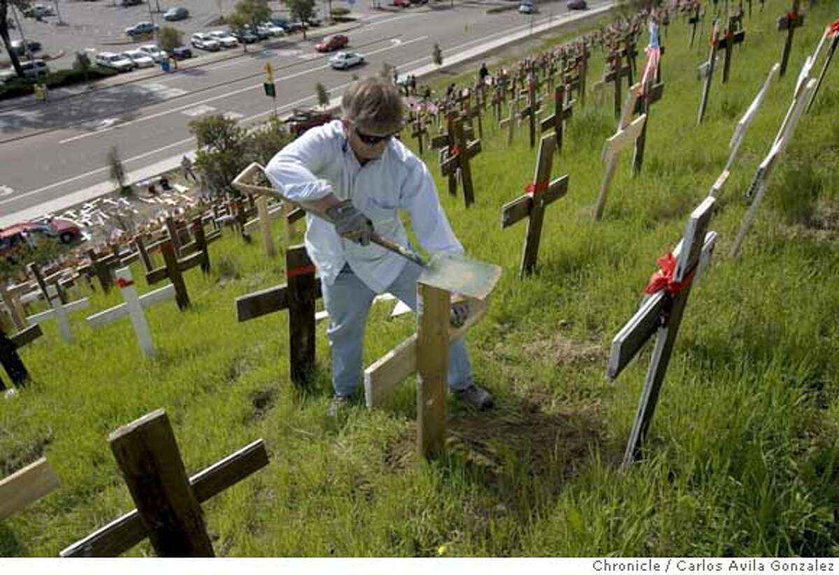 CROSSES05_006_CAG.CR2 John Eaton, of Lafayette, places a new cross on the anti-war memorial ion the hillside along Highway 24. Volunteers added about 200 new crosses to the controversial Iraq War memorial in Lafayette, Ca., on Sunday, March 4, 2007, enough to represent each of the 3,161 soldiers killed in Iraq since the start of the war. The group, opposed to the war in Iraq, has expanded the stark display overlooking the Lafayette BART station over the past several weeks � gathering in cold weather and at times staging candlelight vigils. Several said blanketing this green hillside with a sea of crosses has reinvigorated their sense of civic activism to a level they haven�t experienced not seen since the Vietnam War. Photo by Carlos Avila Gonzalez/The San Francisco Chronicle Photo taken on 3/4/07, in Lafayette, Ca, USA. **All names cq (source) Ran on: 03-05-2007 Volunteers add crosses to the Iraq memorial in Lafayette. The number of crosses closely corresponds to the number of U.S. soldiers killed in the war.