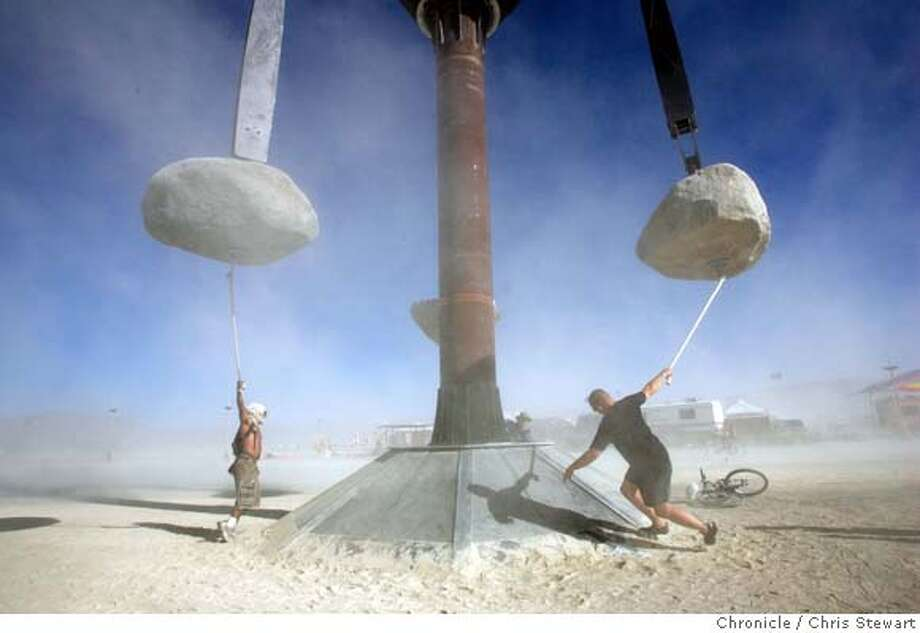 Playful burners brave a dust storm to hang and spin from The Colossus, a massive trio of spinning boulders on the playa. Burning Man 2005 begins Sunday, August 28, 2005 as theme camp burners arrive on the playa. burnman2005  Chris Stewart / The Chronicle Photo: Chris Stewart