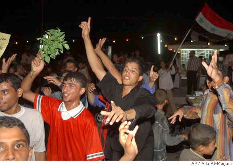 Iraqis celebrate on the streets of the Shiite holly city of Najaf, Sunday, Aug. 28, 2005. Iraqi negotiators finished the country's new constitution Sunday but without the endorsement of Sunni Arabs who helped prepare it, dealing a blow to the Bush administration and setting the stage for a bitter campaign leading up to an October referendum. (AP Photo/Alla Al-Marjani) #######0423210416 Photo: ALAA AL-MARJANI