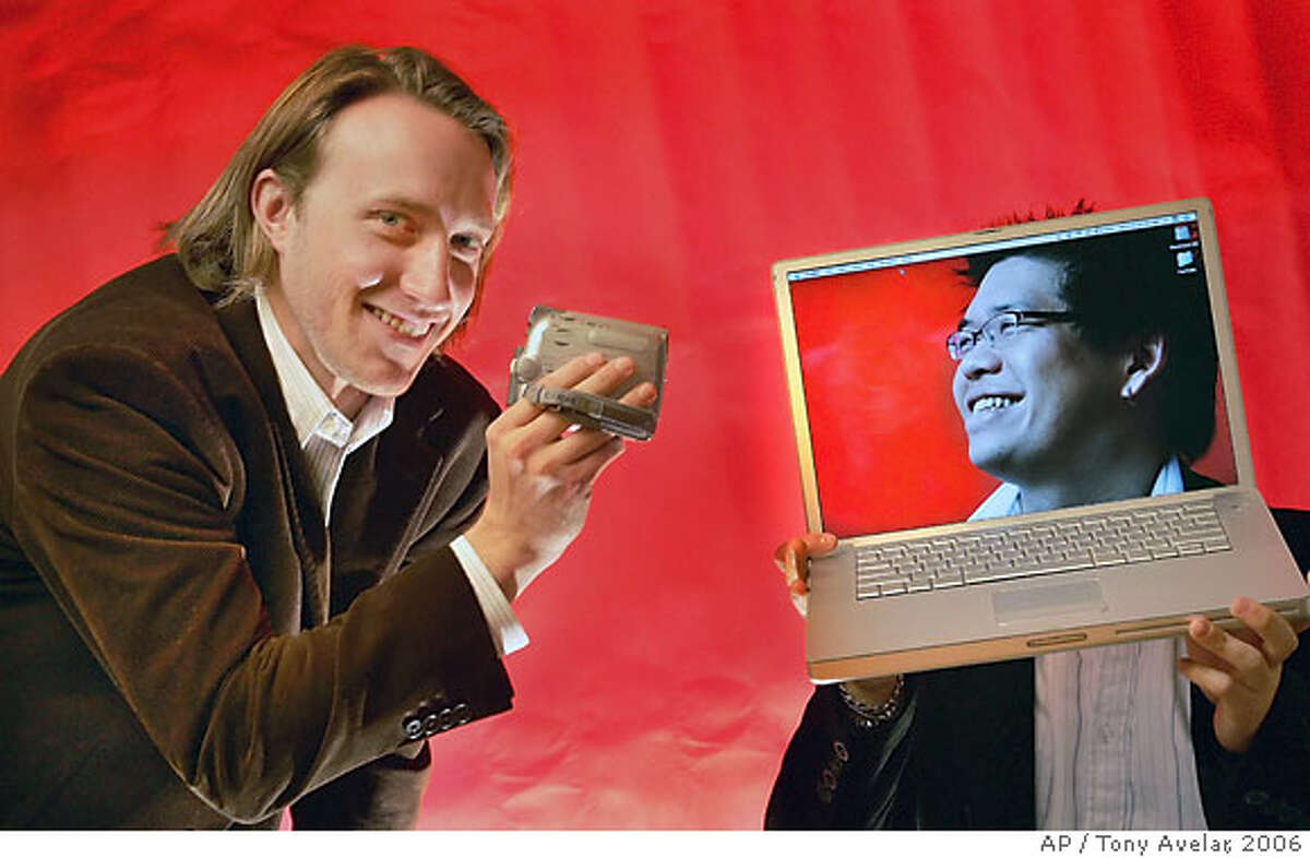 ** FILE ** YouTube cofounders Chad Hurley, 29, left, and Steven Chen, 27, pose for a photo with their laptops at their office loft in a San Mateo, Calif. file photo from March 29, 2006. Internet search leader Google Inc. is in talks to acquire the popular online video site YouTube Inc. for about $1.6 billion, The Wall Street Journal reported Friday, citing a person familiar with the matter. (AP Photo/Tony Avelar, File)