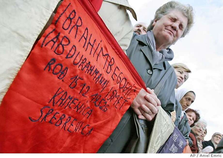 A Bosnian Muslim woman holds banner with names of victims of the Srebrenica masacre during the Bosnian war during a demonstration in Sarajevo, Bosnia, on Tuesday Feb.27, 2007. Thousands of Bosnian Muslim gathered in Sarajevo to protest against a decision ruling by the World Court clearing Serbia of genocide. The International Court of Justice Monday cleared Serbia of committing genocide in the 1992-95 Bosnian war, but said the massacre by Bosnian Serb forces of more than 7,000 Muslim men and boys at the U.N.-protected Srebrenica enclave was an act of genocide. (AP Photo/Amel Emric) Photo: AMEL EMRIC