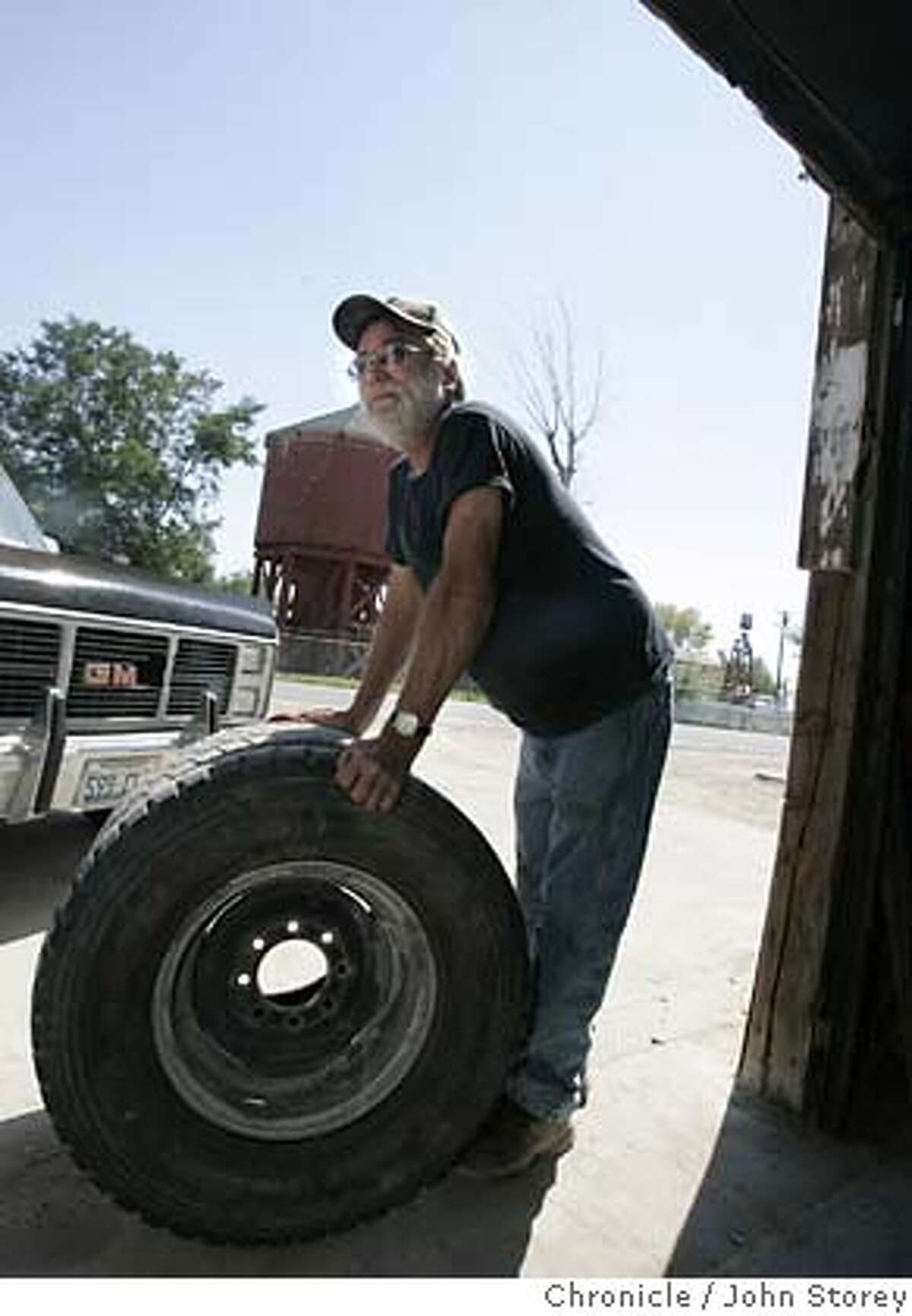 Gerlach_jrs_0100.jpg Everett gates holds a tire he had just repaired at the local auto repair shop. Story about the tiny town of Gerlach, which is the gateway to