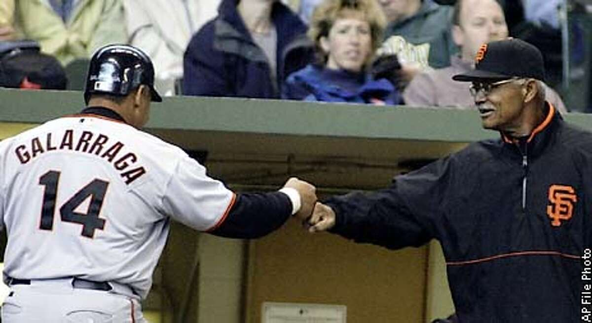San Francisco Giants' Andres Galarraga, left, is congratulated by manager Felipe Alou, after scoring on Kirk Rueter's single in the fourth inning against the Milwaukee Brewers Sunday, April 6, 2003, in Milwaukee. (AP Photo/Darren Hauck)
