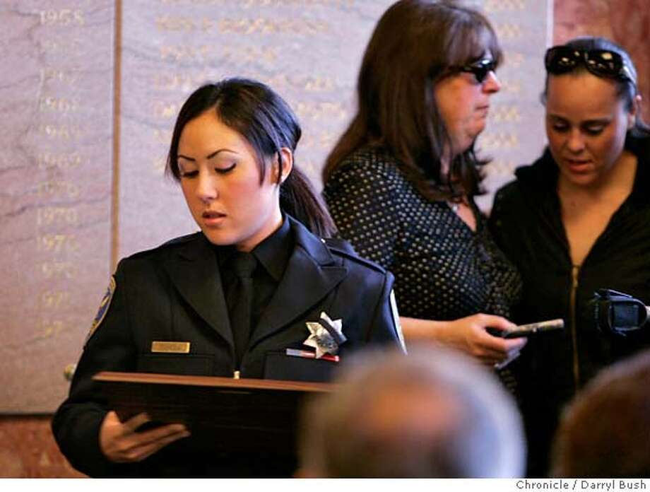 """wall_0003_db.JPG  Widow of slain officer, SFPD officer Salina Tuvera, walks back to her seat after receiving a plaque in honor of her fallen officer husband, Bryan Tuvera, with mother of slain officer, Sandy Tuvera, and sister of slain officer, Tracee Tuvera, far right, in background, after they all took part in an unveiling of the inscribed name of fallen San Francisco police officer, Bryan Tuvera, to the wall of honor which also says, """"IN TRIBUTE TO THE POLICE OFFICERS OF SAN FRANCISCO WHO GAVE THEIR LIVES IN THE LINE OF DUTY"""" inside the lobby at the Hall of Justice in San Francisco, CA, on Friday, March, 2, 2007. photo taken: 3/2/07  Darryl Bush / The Chronicle ** Salina Tuvera, Sandy Tuvera, Tracee Tuvera, (cq) MANDATORY CREDIT FOR PHOTOG AND SF CHRONICLE/NO SALES-MAGS OUT Photo: Darryl Bush"""