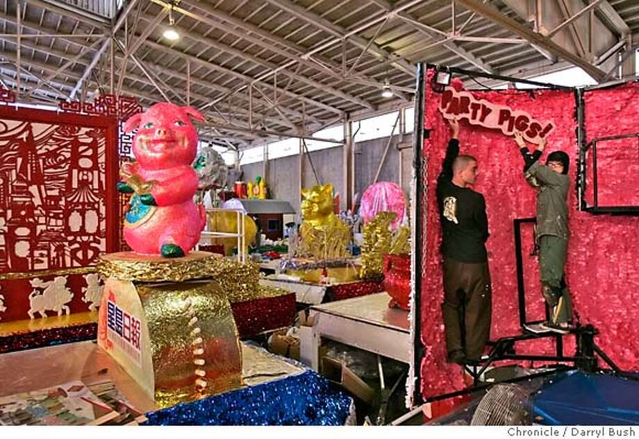 "float_0003_db.JPG  Float artist, Allison Lowe of Castro Valley, and float builder, Robert Lauffer of Mountain View, place signs that say, ""party pigs,"" on a float, as workers from East West Productions, build floats for Chinese New Year's parade inside Pier 27 in San Francisco, CA, on Wednesday, February, 28, 2007. The float to left features a dancing pig. photo taken: 2/28/07  Darryl Bush / The Chronicle ** Allison Lowe, Robert Lauffer (cq) MANDATORY CREDIT FOR PHOTOG AND SF CHRONICLE/NO SALES-MAGS OUT Photo: Darryl Bush"