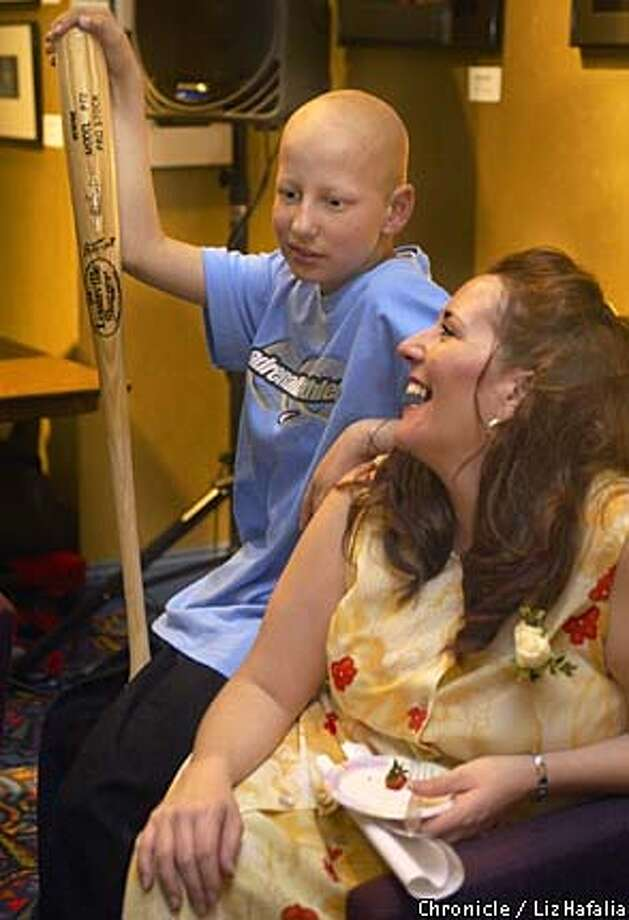 Tyler Woodard, 13 years old, with his mom Kaylynne Reeves. He brought a bat signed by Giant's Marvin Bernard which he got from the Family House annual auction just before coming here, where he will be receiving an award for a movie he made with Bay Kids about cancer. (PHOTOGRAPHED BY LIZ HAFALIA/THE SAN FRANCISCO CHRONICLE) Photo: LIZ HAFALIA
