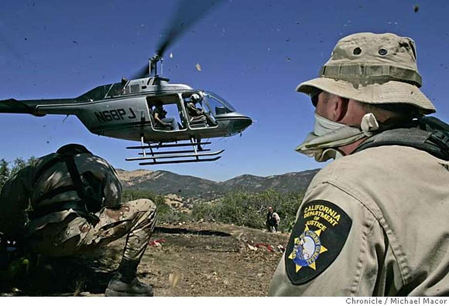 potraid_047_mac.jpg Dept. of Justice personell are flown into the remote area by helicopter. Agents had to clear a landing site for the helicopter by using chain saws and machetes. Some 6,000 marijuana plants were located growing in a remote canyon, the plants removed by state drug agents. In the aftermath of a pot-raid shootout in the Santa Cruz Mountains last month that left a state game warden wounded and an outlaw grower dead, we ride-along with state agents on a pot raid in the remote reaches of southern San Benito County, south of Hollister. 8/25/05 Paicines, Ca Michael Macor / San Francisco Chronicle Mandatory Credit for Photographer and San Francisco Chronicle/ - Magazine Out Photo: Michael Macor