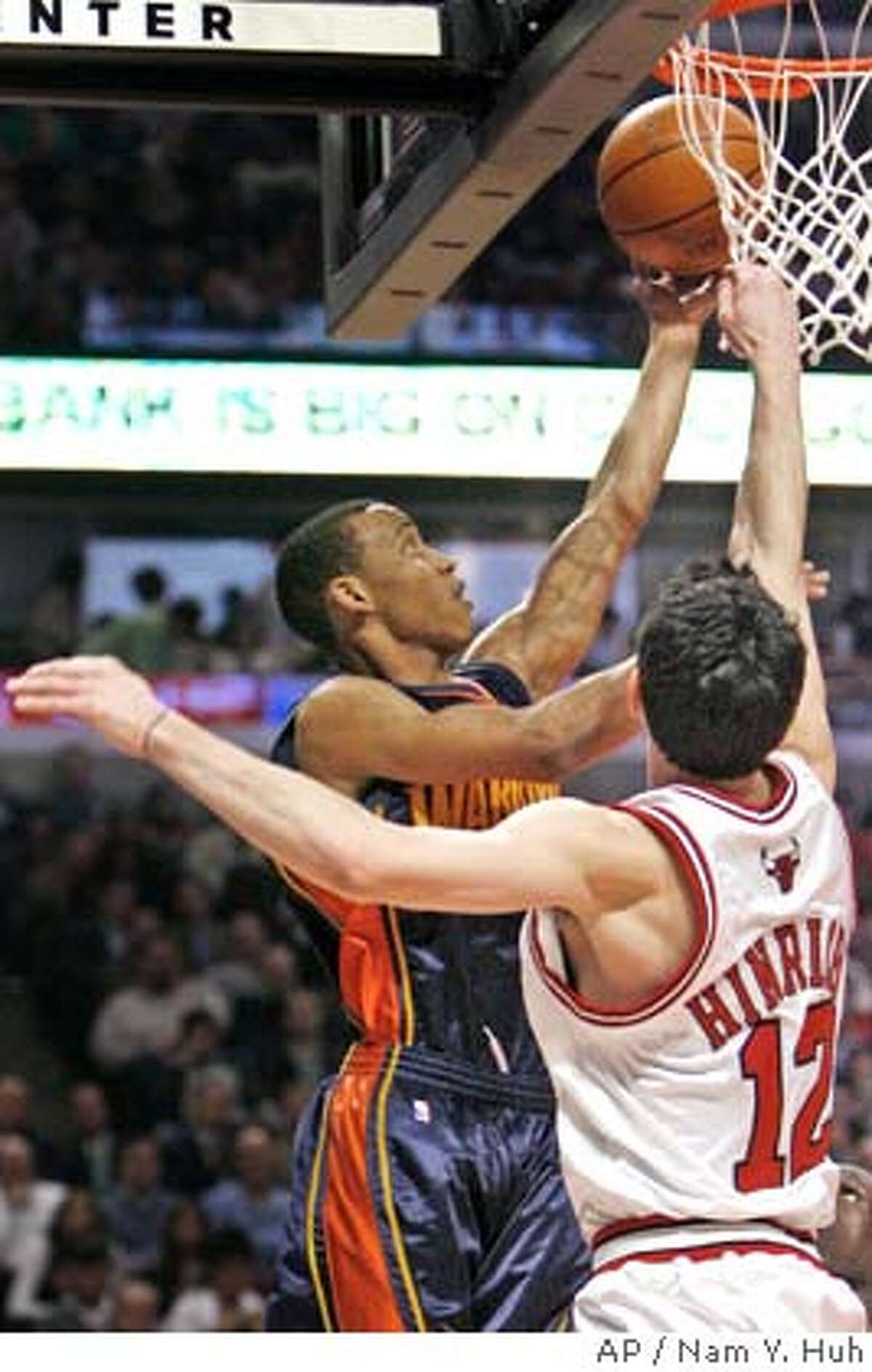 Golden State Warriors guard Monta Ellis, left, goes up for a shot against Chicago Bulls' Kirk Hinrich during the first quarter of an NBA basketball game in Chicago, Wednesday, Feb. 28, 2007.(AP Photo/Nam Y. Huh)