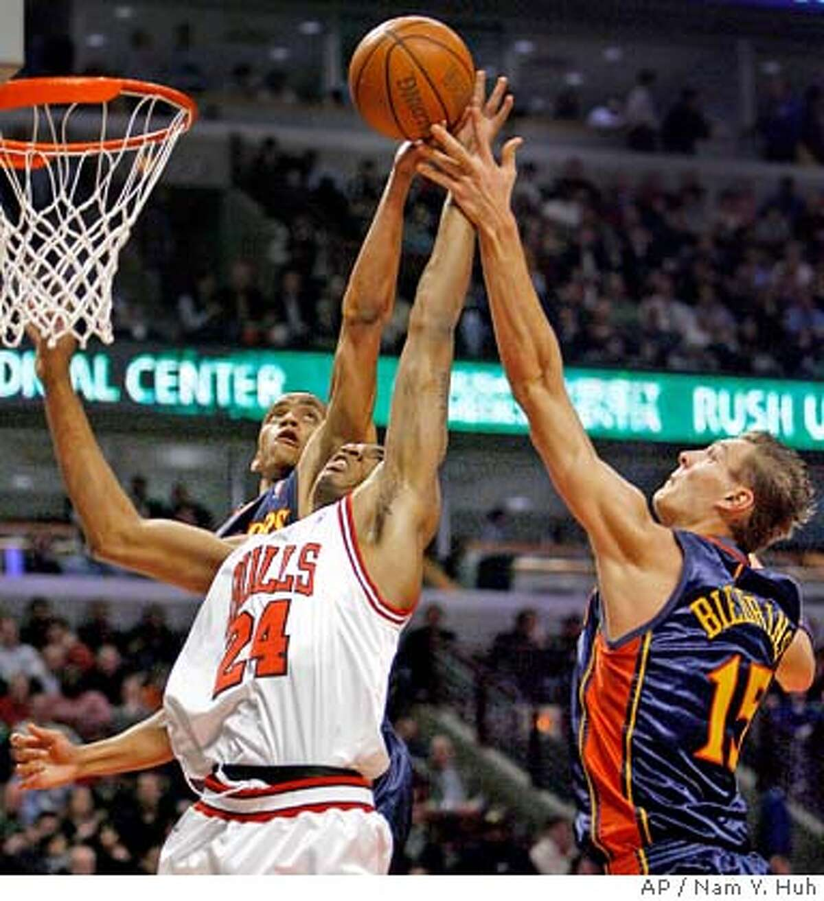 Chicago Bulls' Tyrus Thomas, center, battles for a rebound with Golden State Warriors' Monta Ellis, left, and Andris Biedrins during the first quarter of an NBA basketball game in Chicago, Wednesday, Feb. 28, 2007.(AP Photo/Nam Y. Huh)