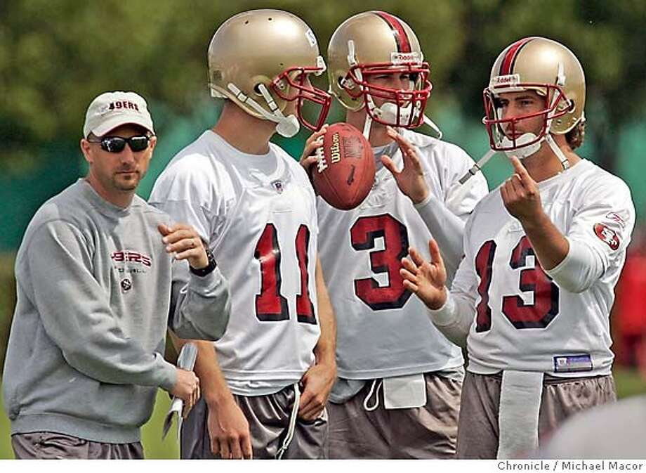49ers QB coach Jim Hostler watches practice with three of his charges -- Alex Smith (11), Cody Pickett (3) and Tim Rattay (13) in May 2005. Photo: Michael Macor