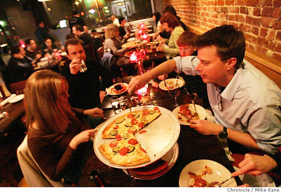 BARGAINBITE01_004_MBK.jpg  Chris Boyd, right, serves up a slice of pizza at Little Star Pizza on Valencia in San Francisco, CA, on Tuesday, February, 20, 2007. Clockwise from lower left is Lisa Thogmartin, Tom Boyd, and Blake Anderson. photo taken: 2/20/07  Mike Kane / The Chronicle ** Chris Boyd, Lisa Thogmartin, Tom Boyd, and Blake Anderson Photo: MIKE KANE