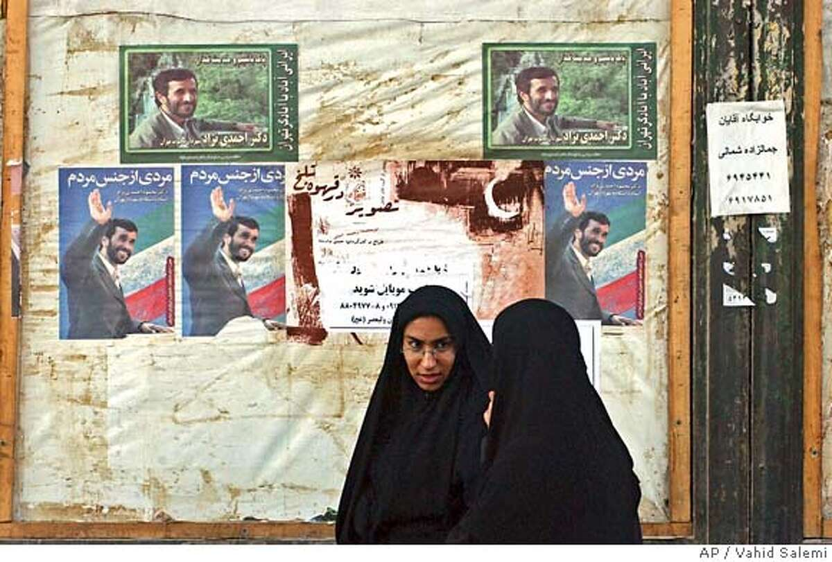 Two Iranian veiled women, walk past campaign posters of Tehran's hardline mayor, Mahmoud Ahmadinejad, for presidential elections, at the Enqelab (Revolution) St. in Tehran, Iran, Sunday, June 19, 2005. The man who said: