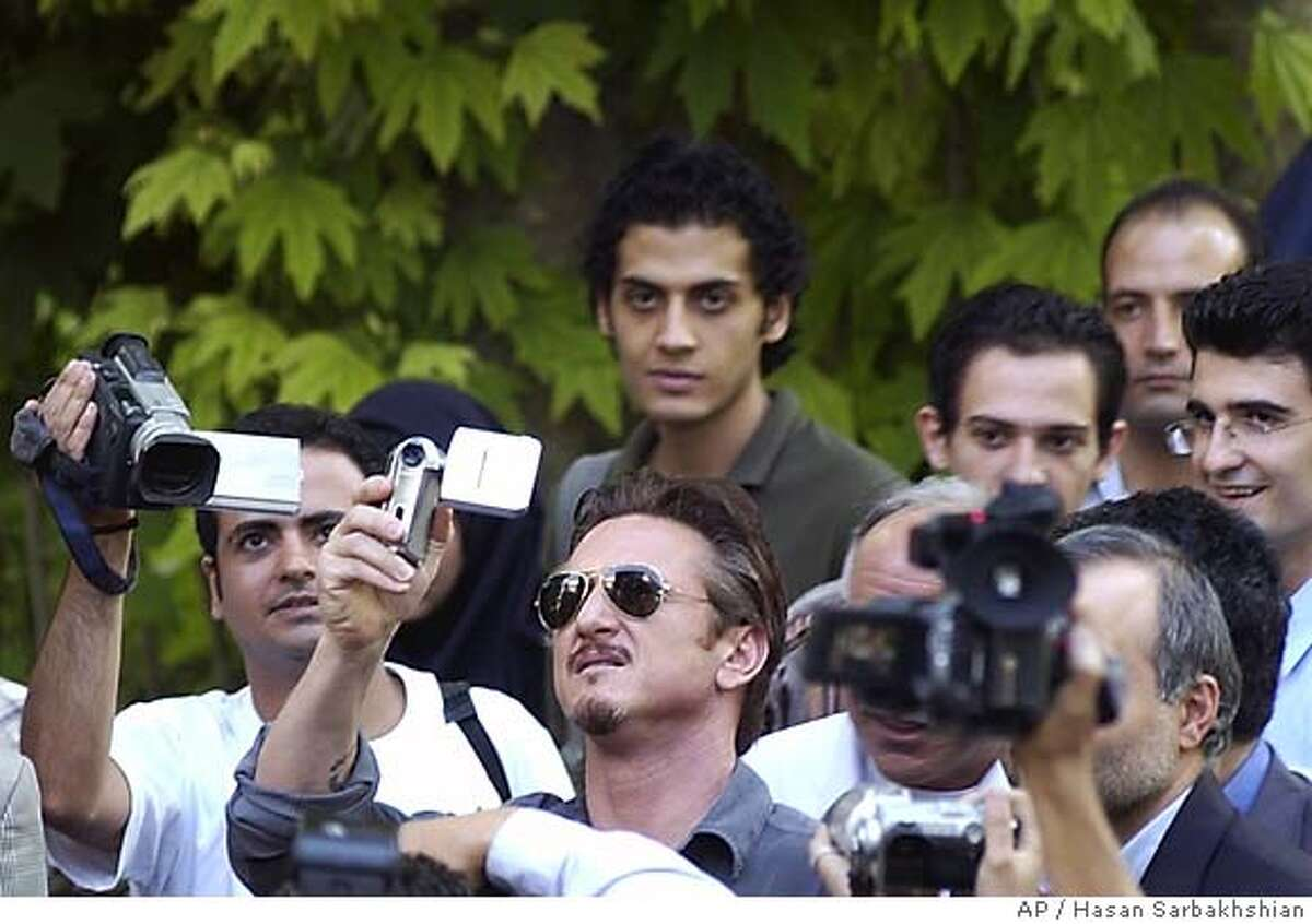 Oscar-winning U.S. actor Sean Penn, center, records with his camera during a visit to Iran's Cinema museum in Tehran Monday, June 13, 2005. Sean Penn, 44, arrived in Iran as a reporter for the San Francisco Chronicle ahead of presidential elections on Friday. (AP Photo/Hasan Sarbakhshian)