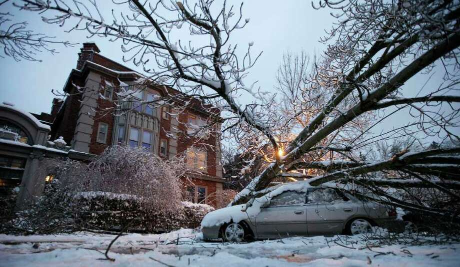 A tree rests on a car, Thursday, Jan. 19, 2012, in front of an apartment building in Tacoma, Wash. On the heels of heavy snow that fell Wednesday, the Western Washington region was hit with an ice storm Thursday that coated trees and vehicles with a heavy coat of ice. Photo: Ted S. Warren / ASSOCIATED PRESS