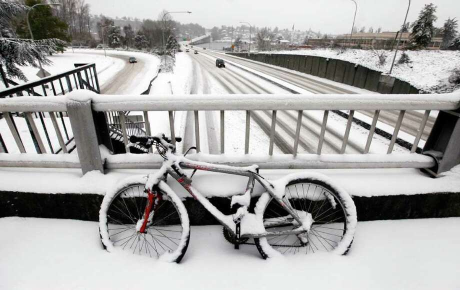 A snow-covered bicycle is locked to a bridge as unusually light traffic drives past below on Highway 520 near the University of Washington Thursday, Jan. 19, 2012, in Seattle. A monster Pacific Northwest storm coated the Seattle area in a thick layer of ice Thursday and brought much of the state to a standstill, sending hundreds of cars spinning out of control, temporarily shutting down the airport and knocking down so many trees that members of the Washington State Patrol brought chain saws to work. Photo: Elaine Thompson / ASSOCIATED PRESS