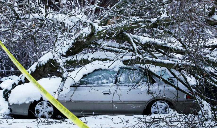 A tree rests on a car, Thursday, Jan. 19, 2012, in Tacoma, Wash. On the heels of heavy snow that fell Wednesday, the Western Washington region was hit with an ice storm Thursday that coated trees and vehicles with a heavy coat of ice. Photo: Ted S. Warren / ASSOCIATED PRESS