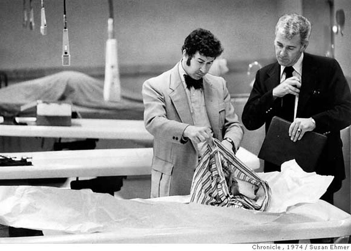 """In this photo from March 29, 1974, San Francisco homicide inspectors David Toschi, left, and William Armstrong go through a murder victim's clothes at the morgue in the Hall of Justice in San Francisco. The Zodiac killer is blamed for at least five murders in 1968 and 1969 in the San Francisco Bay Area. He was never caught, though many, including Graysmith, believe he was Arthur Leigh Allen, a Vallejo man who who died in 1992. The $80 million film, """"Zodiac,"""" based on the 1986 true-crime book by Graysmith, was shot in 2005 in the San Francisco Bay area. (AP Photo/The San Francisco Chronicle, Susan Ehmer)"""