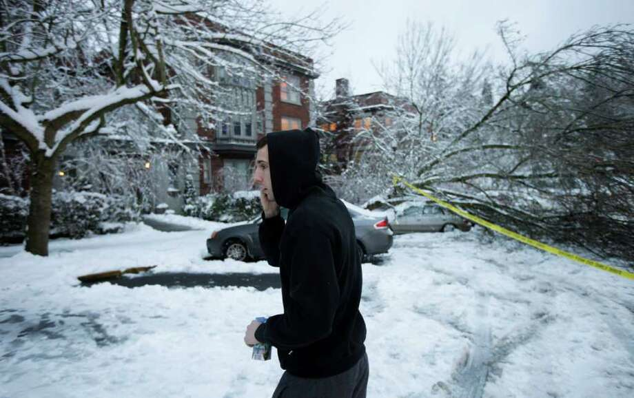 Sam Doyle talks on the phone near where a tree fell on his car, Thursday, Jan. 19, 2012, in Tacoma, Wash. On the heels of heavy snow that fell Wednesday, the Western Washington region was hit with an ice storm Thursday that coated trees and vehicles with a heavy coat of ice. Photo: Ted S. Warren / ASSOCIATED PRESS