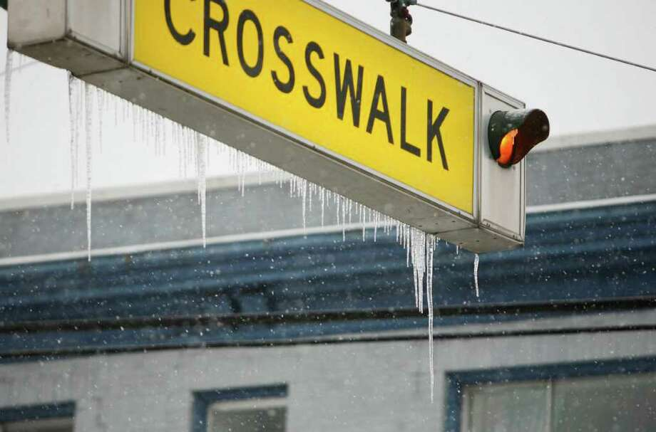 Icicles hang from a crosswalk sign on 12th Ave. and Marion St. in Seattle on Thursday, Jan. 19, 2012. Thursday's ice storm caused at least 200,000 homes in the Seattle area to lose power by midday. Photo: LINDSEY WASSON / SEATTLEPI.COM
