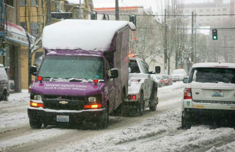 A delivery truck is towed away in the snow on 11th Ave. and Pike St. on Thursday, Jan. 19, 2012. Thursday's ice storm caused at least 200,000 homes in the Seattle area to lose power by midday. Photo: LINDSEY WASSON / SEATTLEPI.COM