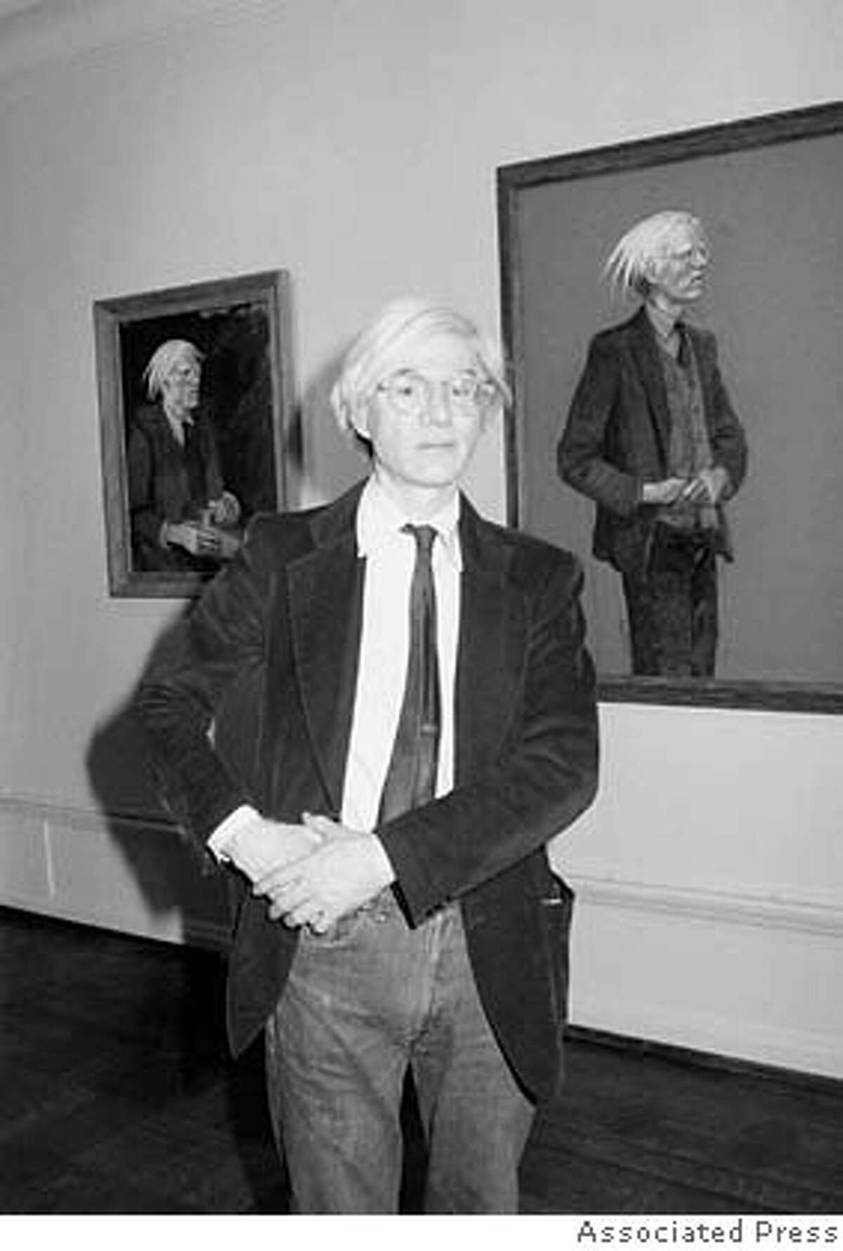 Pop artist Andy Warhol poses in front of a portrait of himself at the show Andy Warhol and Jamie Wyeth: Portraits of Each Other at the Coe Kerr Gallery in New York City on June 3, 1976. (AP Photo)