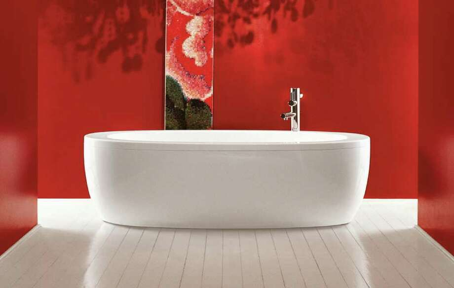 The Il Bagno tub by Alessi for Laufen, above, is sleek and simple. Below, the silver travertine of the Papillon bathtub by Stone Forest evokes elegance and organic simplicity.
