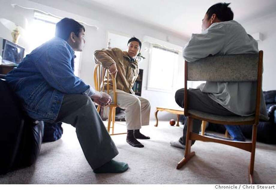"""�burma_299_cs.jpg Yan Aung (right) visits with fellow Burmese Anil Verma (left, blue denim jacket - back to camera) and Maung Maung Latt (center, brown jacket) in Yan Aung's Oakland home. In 1988, Yan Aung was a student democracy advocate in Rangoon. When Burma's army massacred thousands of student-demonstrators that year, Yan Aung fled to the hills on Burma's """"underground railroad"""" and joined one of the armed resistance groups. In 1994 he took over the Popular Democratic Front where he met, at the time, its only woman-soldier, San San Win. The two were married. They have since moved to Oakland and live among several other Burmese refugees with their 13-year-old daughter Thunder (really) and son Nyein Chan, five-years-old. Chris Stewart / The Chronicle MANDATORY CREDIT FOR PHOTOG AND SF CHRONICLE/NO SALES-MAGS OUT Photo: Chris Stewart"""