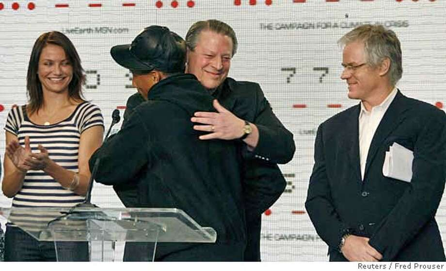 Producer and singer Pharrell Williams (C) is hugged by former U.S. vice president Al Gore, as actress Cameron Diaz (L) and producer Kevin Wall attend a news conference for the 'Live Earth' concerts in Los Angeles, California February 15, 2007. The planned July 7, 2007 concerts will take place in Sydney, Johannesburg, London and other cities to mobilize action to stop global warming. REUTERS/Fred Prouser (UNITED STATES) Photo: FRED PROUSER