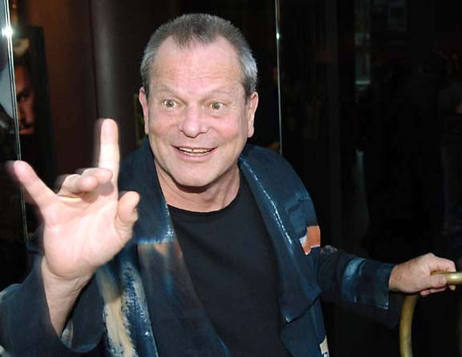 """Terry Gilliam, director of the new film """"The Brothers Grimm,"""" gestures to photographers before heading into the Los Angeles premiere of the film at the Directors Guild of America in West Hollywood, Calif., Monday, Aug. 8, 2005. (AP Photo/Chris Pizzello) Photo: CHRIS PIZZELLO"""