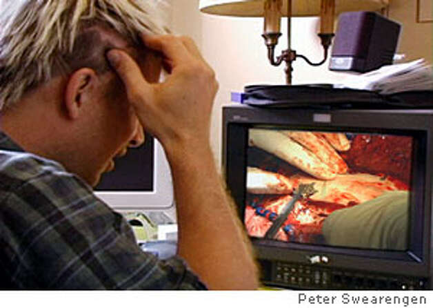 photo where i'm watching footage of the (my) surgery, credit courtesy of peter swearengen, magazine 8/21/05 one time use only Ran on: 08-21-2005  Above: Filmmaker Peter Swearengen, post-surgery, with a brain model; far left, Swearengen watching a clip of his surgery, scar visible; left, wired for research.