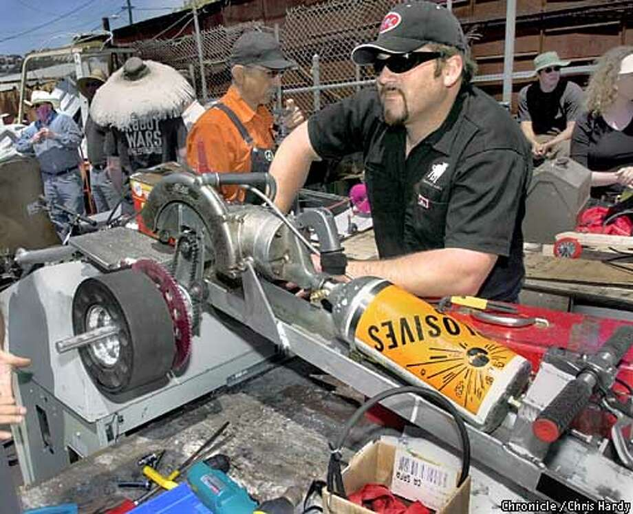"""Power Tool Drag Races! Just what it sounds like. Gearhead creative types gather to show off their bastardized, custom-retrofitted power tools. Sponsored by a group called QBox, a nonprofit that specializes in """"kinetic"""" art (robots and mechanical contraptions). Part of a larger piece on the recent proliferation of electronic and mechanical art -- the Robot Wars craze, for instance.  5/11/03 in San Francisco.  CHRIS HARDY / The Chronicle Photo: CHRIS HARDY"""