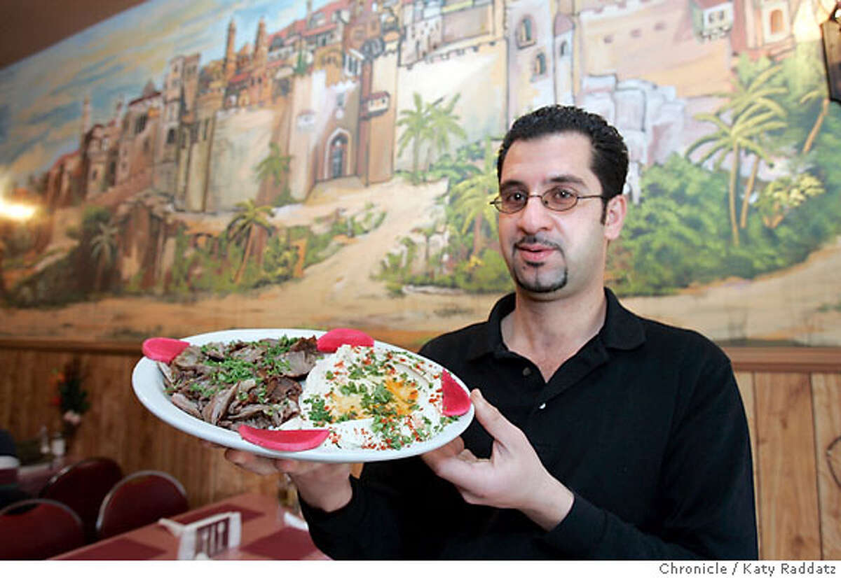 BARGAIN22_007_RAD.jpg SHOWN: Mohammad Hasan, one of the owner/partners, holds a Beef and Lamb Shawerma Platter, with the beautiful murals on the restaurant walls in the background. Old Jerusalem, a Middle Eastern restaurant at 2976 Mission St. in San Francisco. These pictures were made on Monday, Feb. 12, 2007, in San Francisco, CA. (Katy Raddatz/SF Chronicle) **Mohammad Hasan, Shawerma