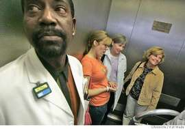 On 7/28/05 in San Francisco (L to R) Kenny Ates (CQ), the front desk receptionist for Radiology and X takes Alicia Parlette, her colleague Kathleen Sullivan and her surrogate mom, Sally Valentine down the elevator for her MRI scans at UCSF. Kat Wade/ The Chronicle