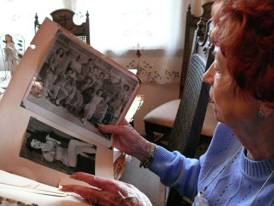 Stratford resident Elinor Kavanaugh looks over a photo album and pictures of her early years as a dancer, entertaining the troops during WWII. Kavanaugh is the director of the Elderberries, a musical variety group at the Fairfield Senior Center. Photo: Genevieve Reilly / Fairfield Citizen
