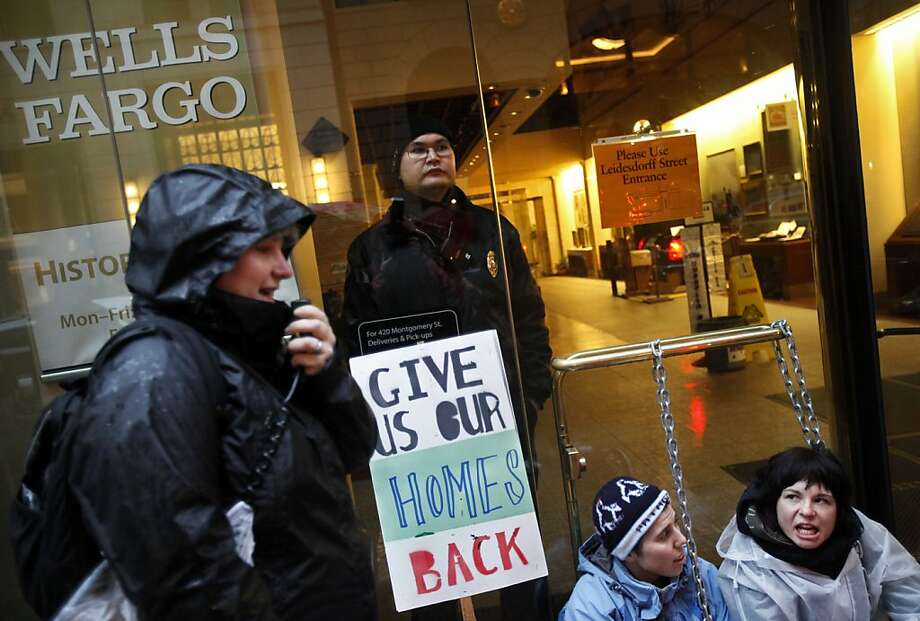 Paulina Nowicka (right) and Sasha Wright (second from right) both of Oakland, California, sit chained to the door of a Wells Fargo bank in protest as part of Occupy Wall Street West's day of action January 20, 2012 in San Francisco, California. Occupy Wall Street West protestors blockaded all the entrances to the bank as part of a day of action. Photo: Sarah Rice, Getty Images