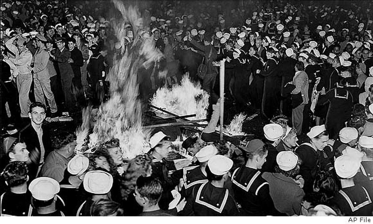 """Crowds celebrated around a bonfire in the middle of San Francisco's Market Street in the early morning hours of Aug. 14, 1945, after newspaper headlines proclaimed """"Tokyo Radio Says Japs Quit."""" Sidewalk war bond booths provided fuel for the fire. Associated Press"""