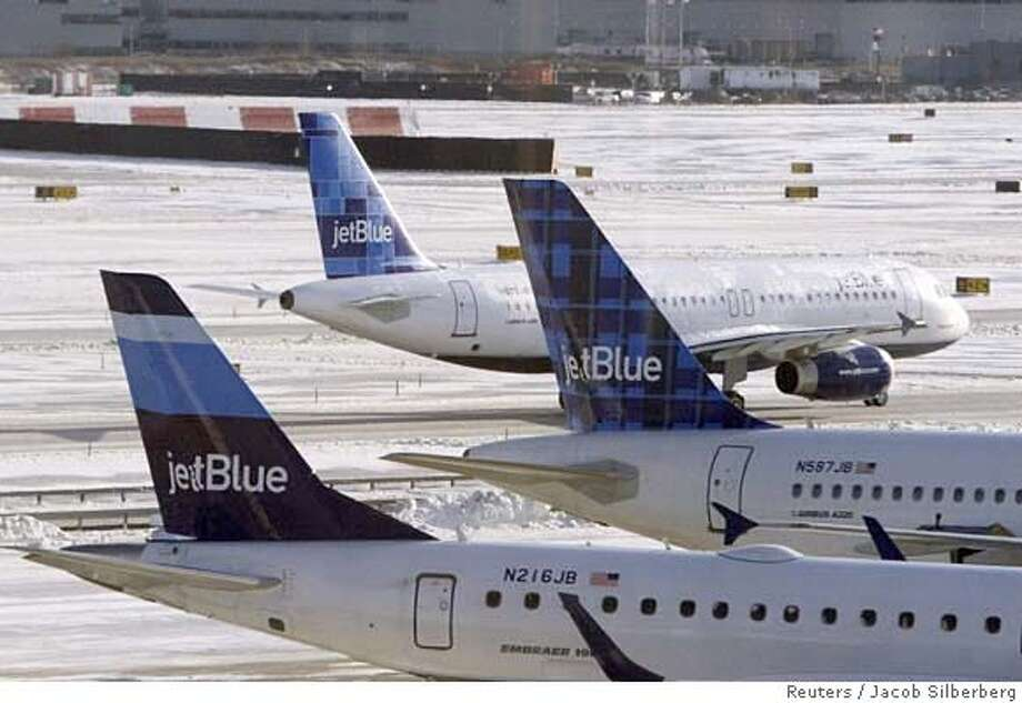 Jet Blue airplanes are see at JFK Airport in February 15, 2007. A winter storm roared into the northeastern United States on Wednesday, dumping a mixture of snow, ice, sleet and rain that caused transportation havoc and forced many schools to close. REUTERS/Jacob Silberberg (UNITED STATES) Photo: JACOB SILBERBERG