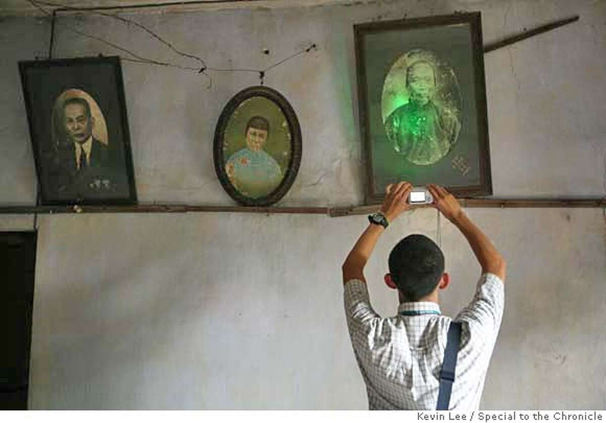 KaiPing, Guang Dong, CHINA - JULY 6: Brian Jamie Lee takes pictures of his ancestors's portrait, in his ancestral home at a village near KaiPing city, Guang Dong province, China on 6 July 2006. (Photo by Kevin Lee for San Francisco Chronicles) Ran on: 02-18-2007 Brian Lee of San Anselmo takes pictures of his ancestors portraits in Chinas Guangdong province during a visit to his ancestral village.