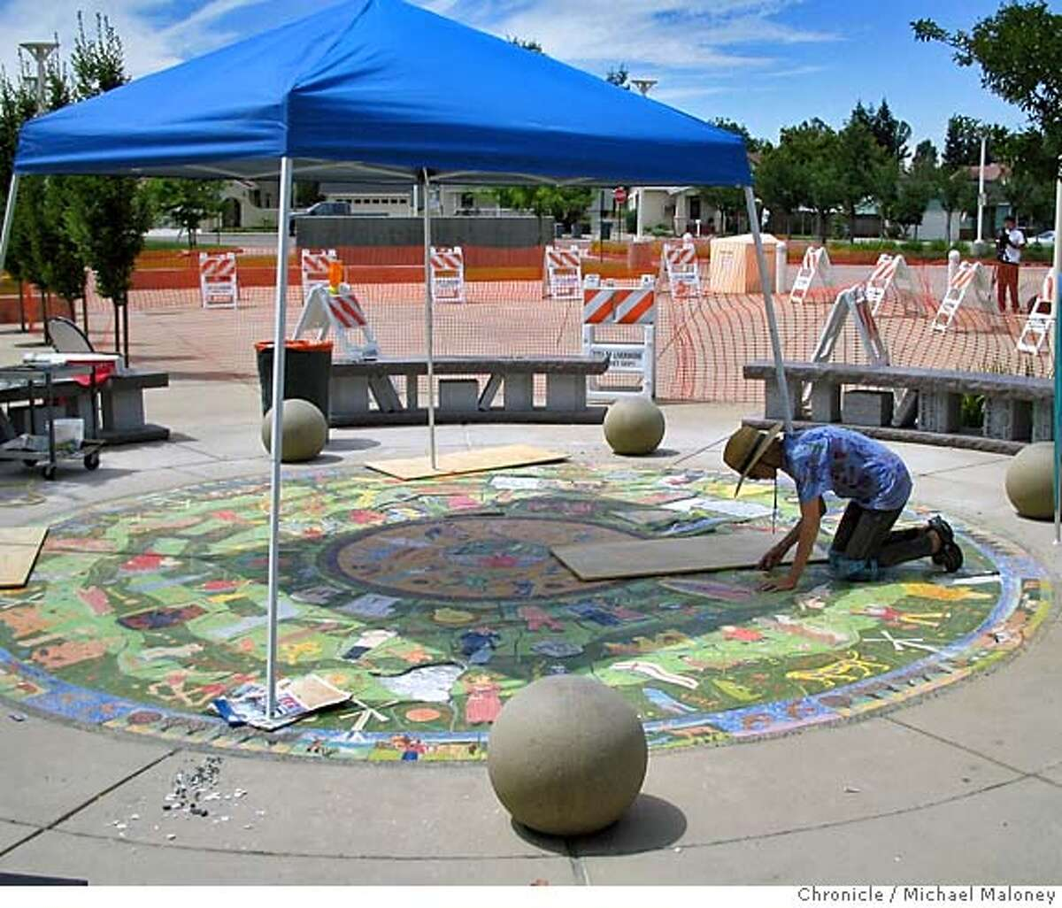Miami artist Maria Alquilar works on her art piece outside the front entrance to the Livermore library. Miami artist Maria Alquilar arrived in Livermore Sunday to correct the $40,000 ceramic mural she created outside Livermore's new public library. She replaced the tiles containing misspelled names of Einstein, Shakespeare, Vincent Van Gogh, Michelangelo and seven other historical figures. Photo by Michael Maloney / San Francisco Chronicle
